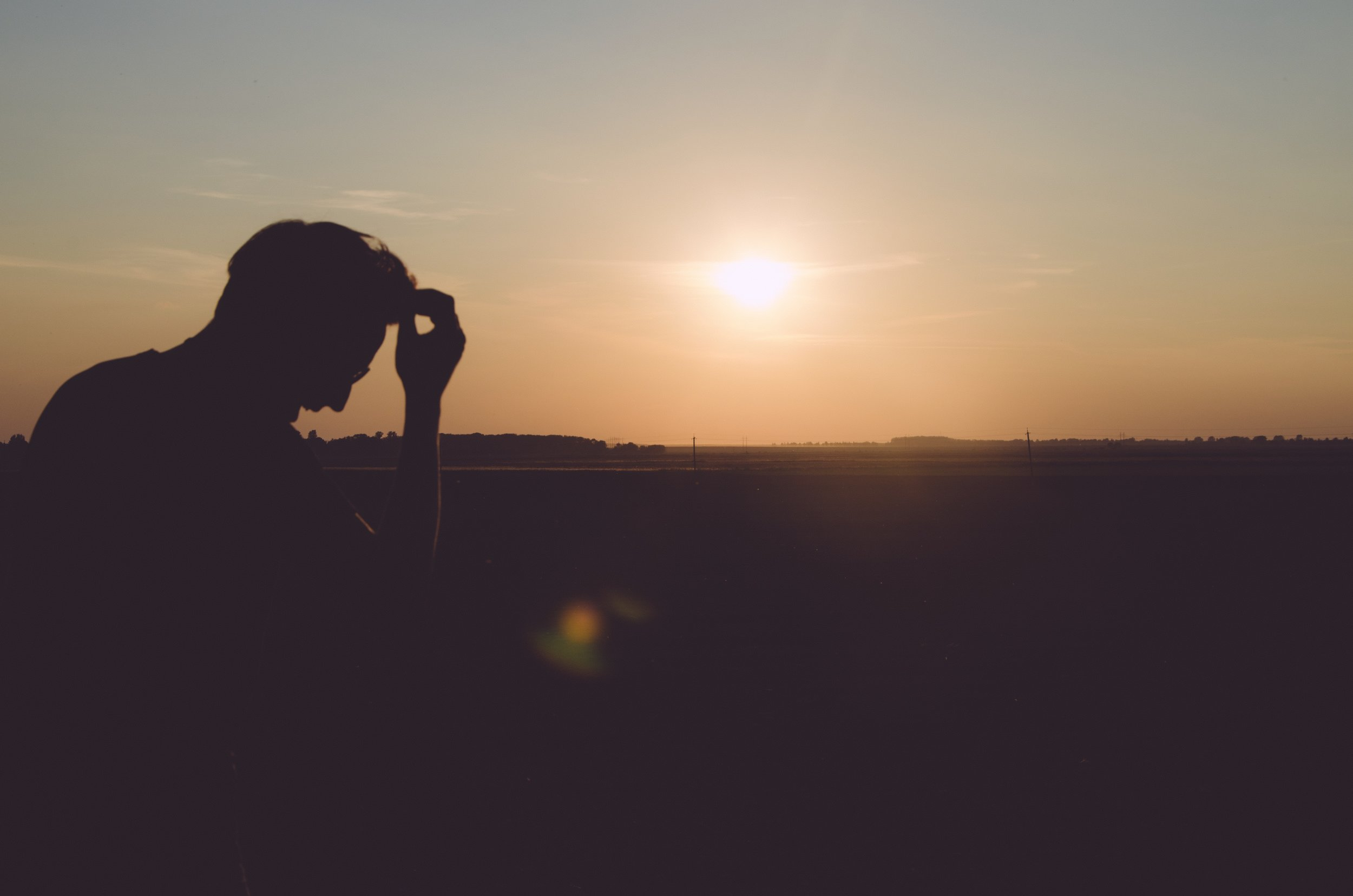 Overthinking man with sun setting in background