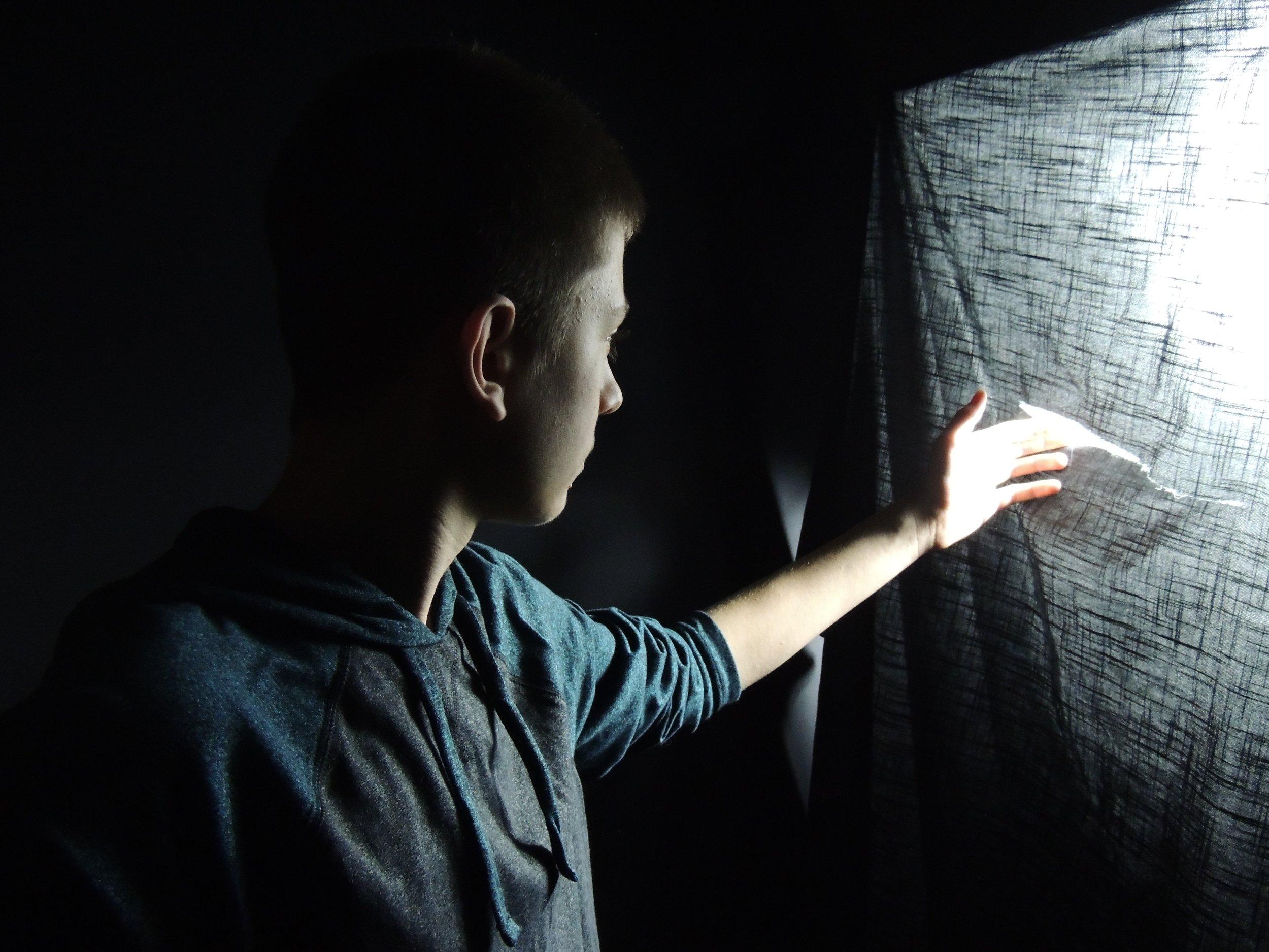 Boy looking at light through tear in sheet