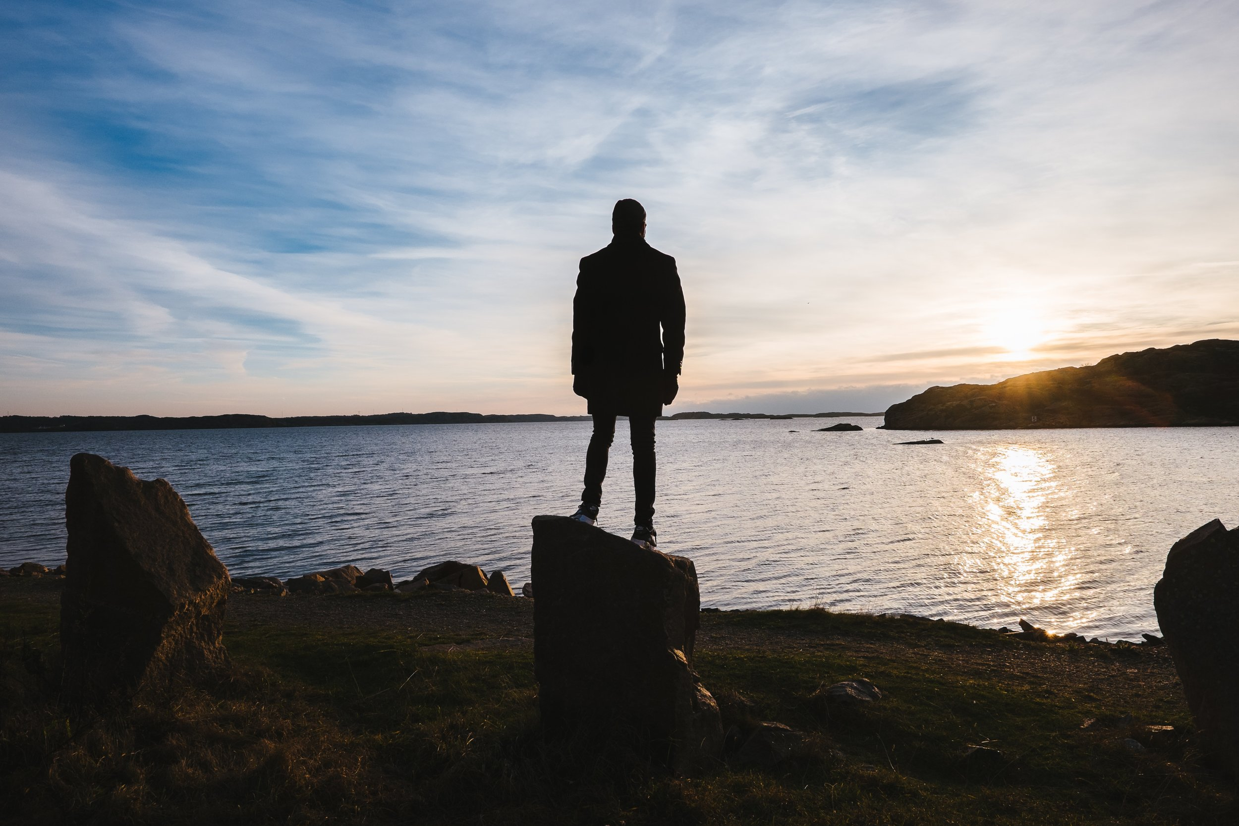 Anxious man standing on rock looking at sunset over water