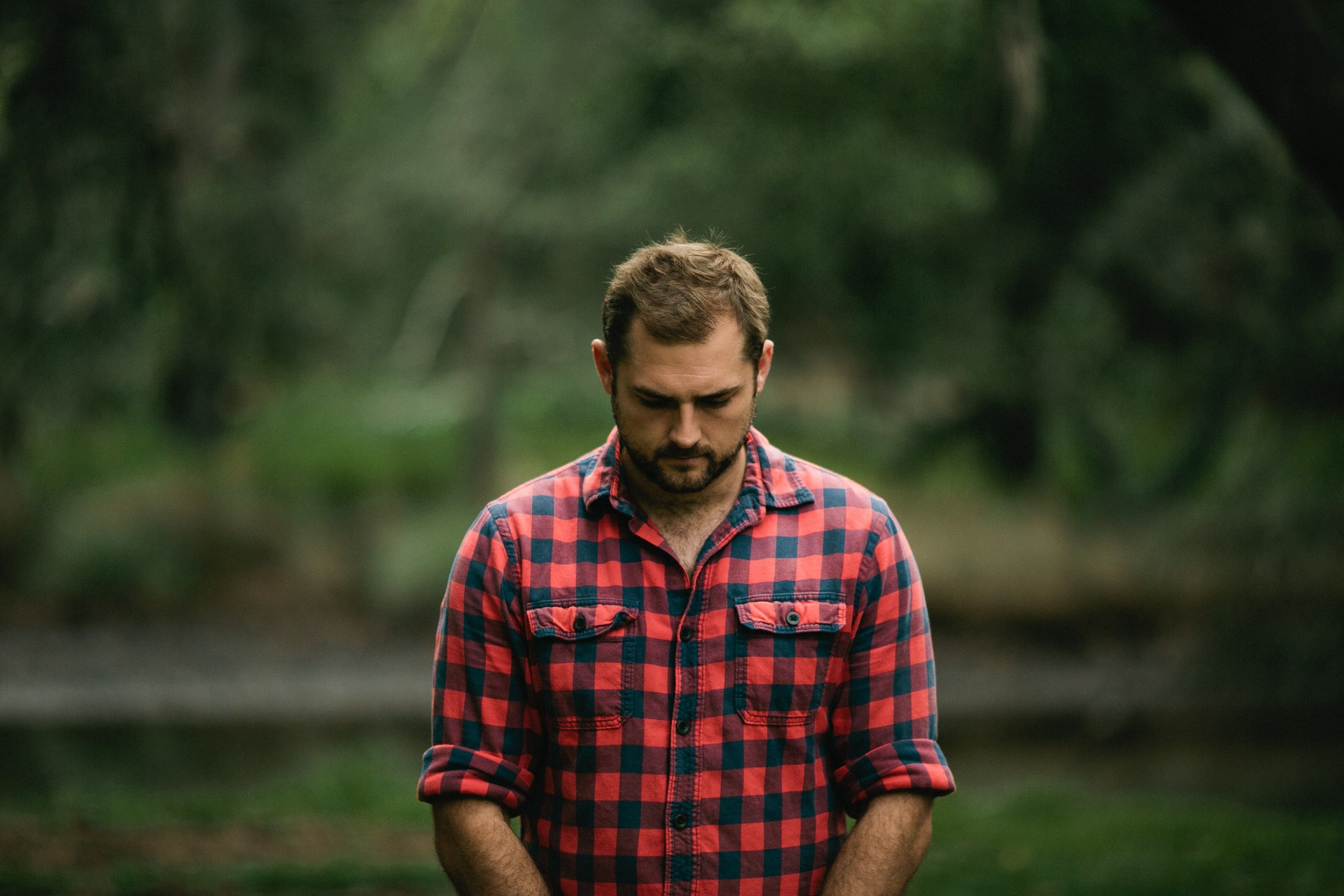 sensitive emotional bearded man with plaid shirt looking downward