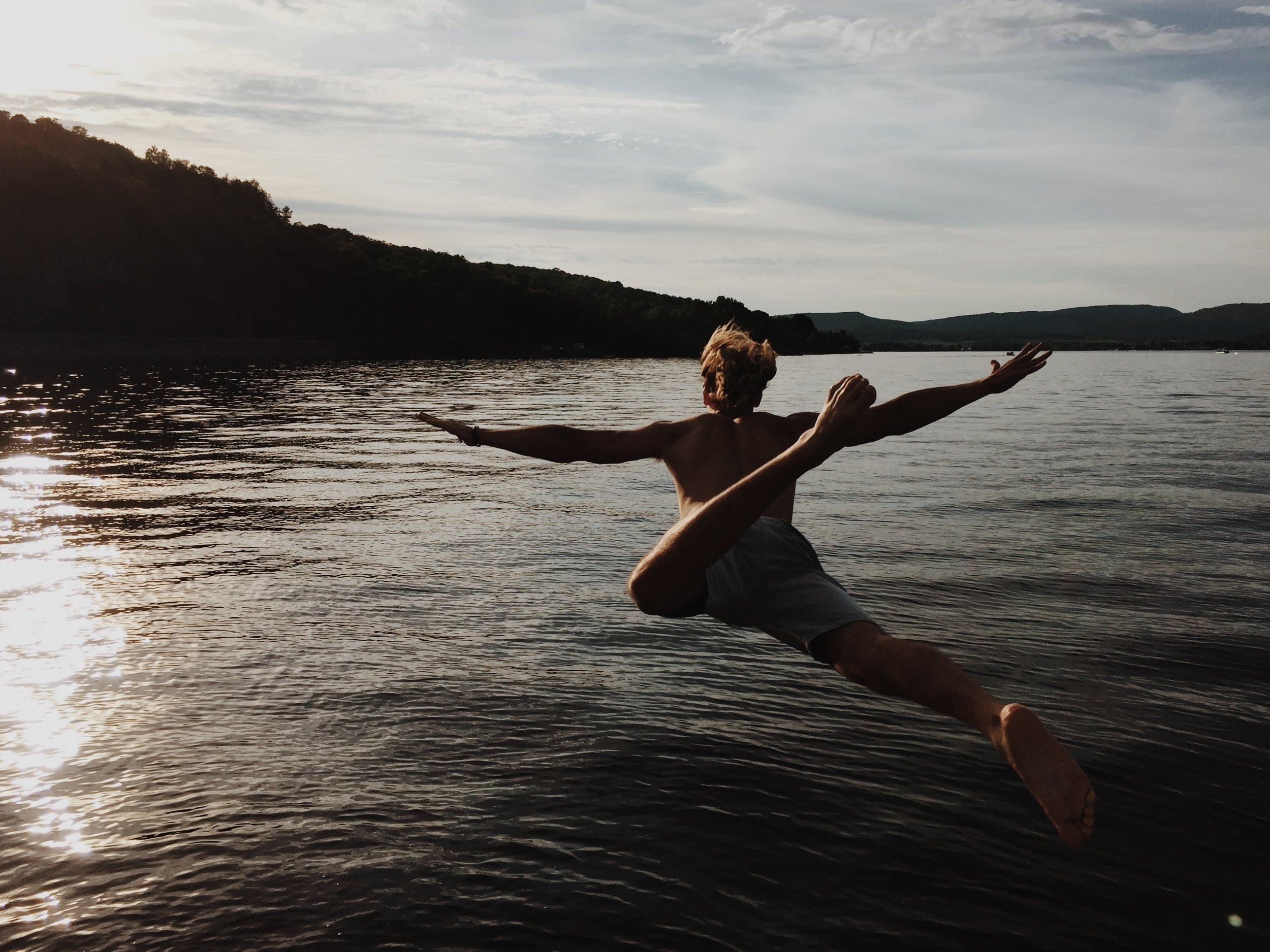 man in bathing suit jumping into lake with arms stretched out like an airplane