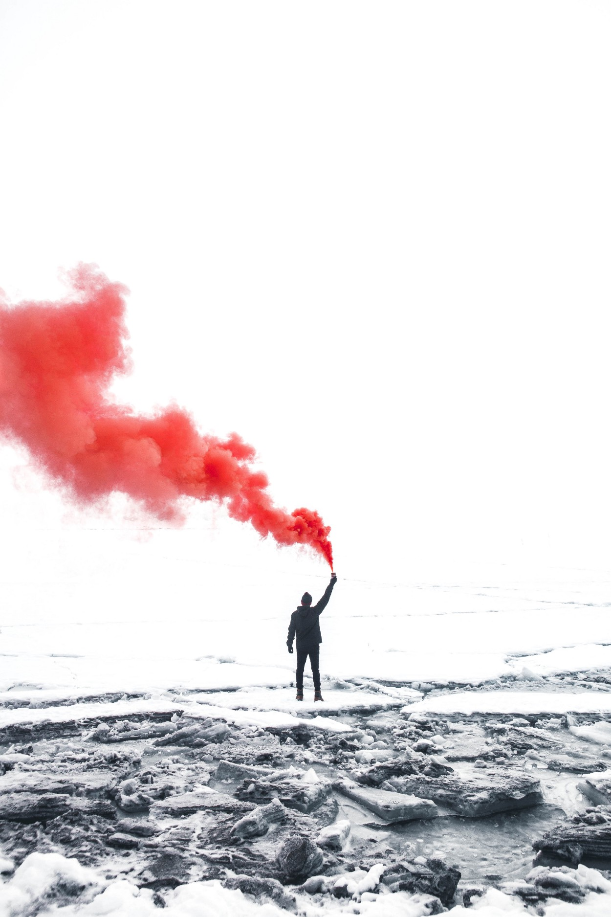man holding up object releasing red smoke