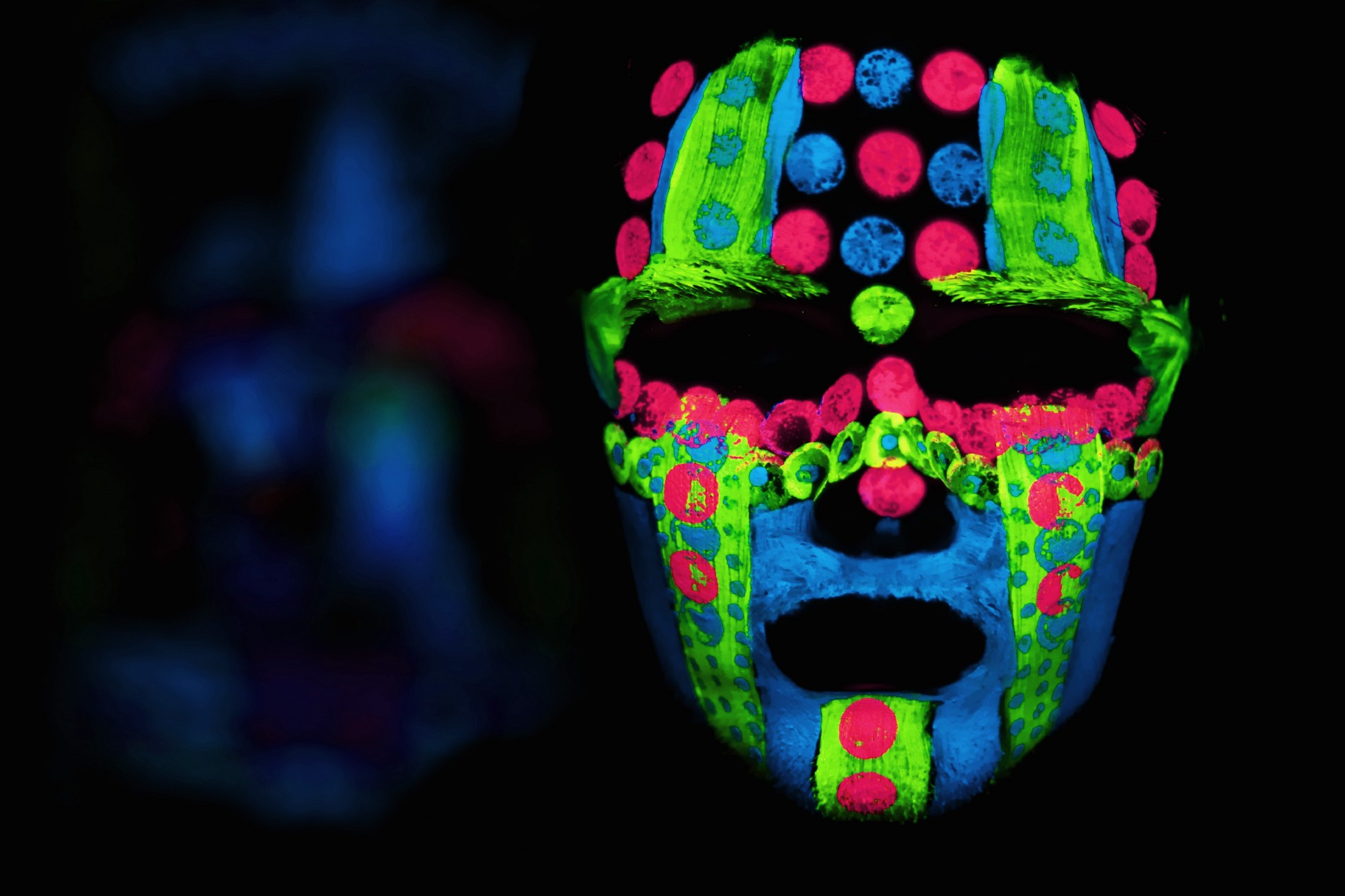 man's face in the dark with neon multicolored paint