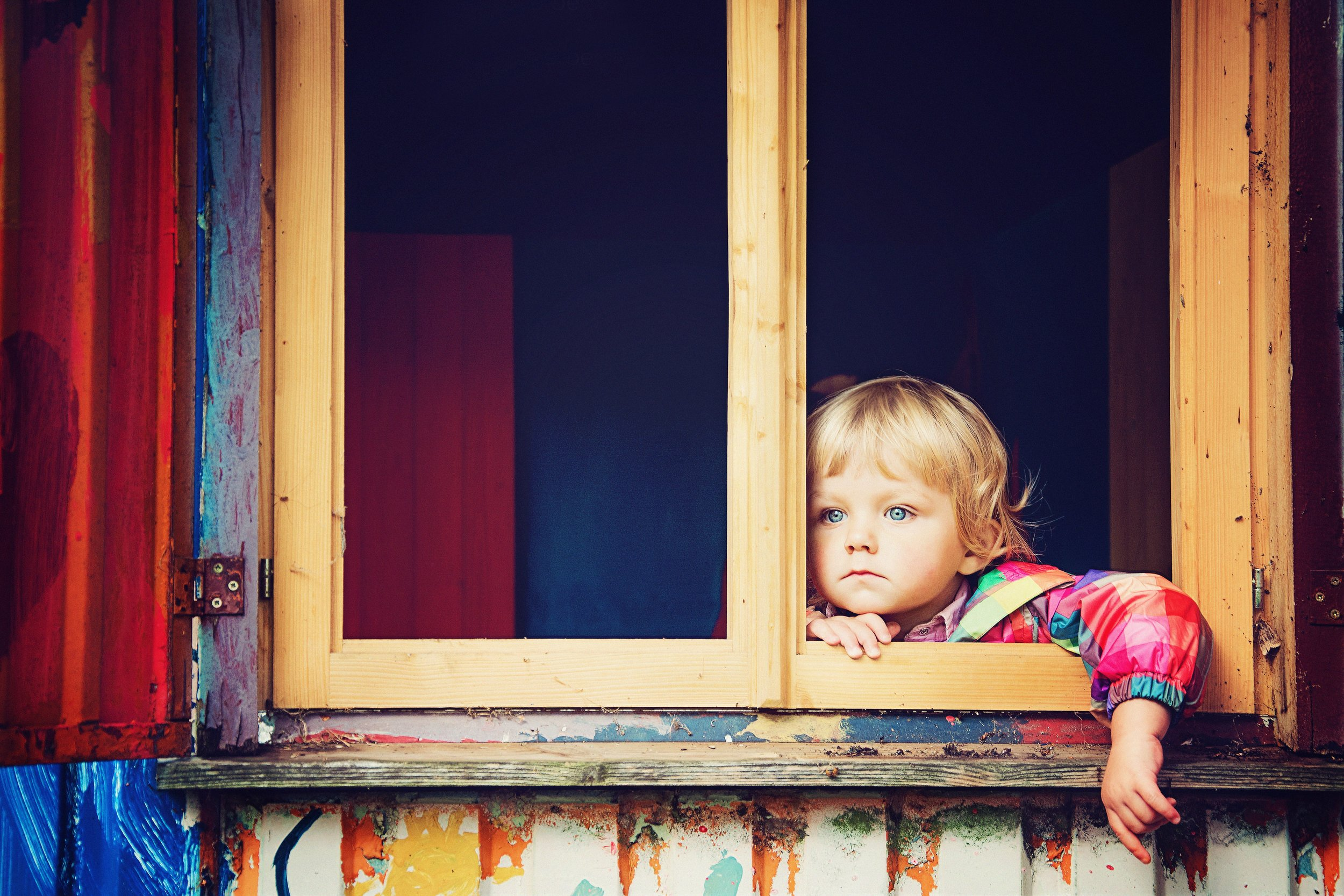 anxious OCD child with distant expression looking out window of house