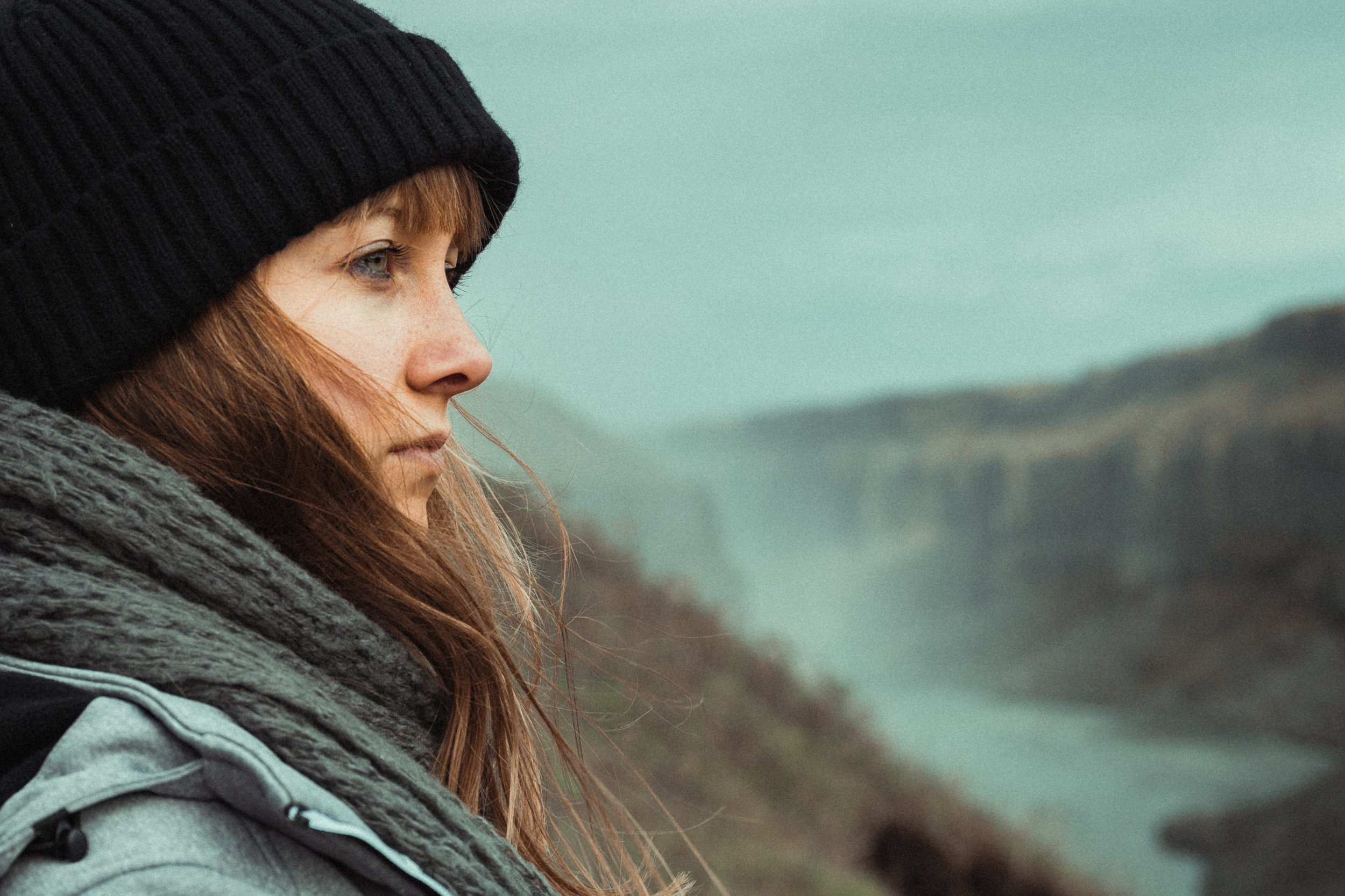 anxious woman dressed for winter staring into distance with river in background