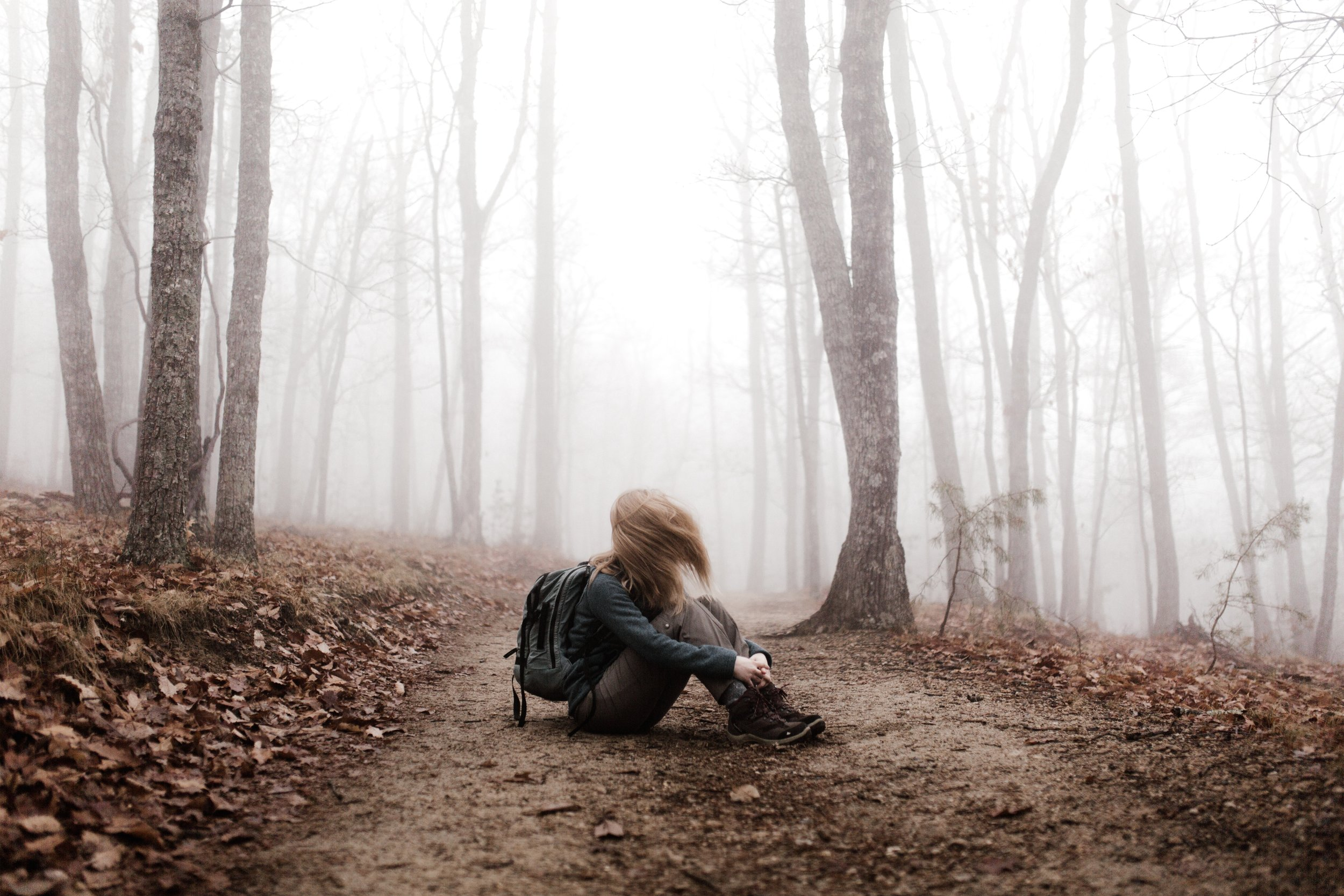 depressed woman sitting on dirt path in foggy forest