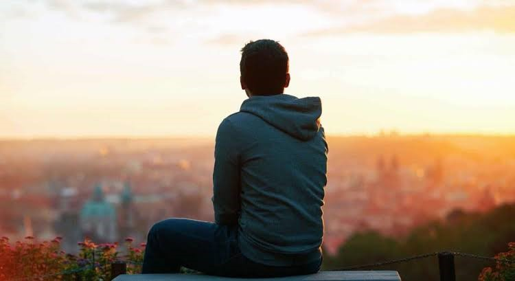 teenager boy sitting on ledge looking at city skyline