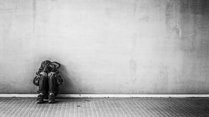 depressed boy sitting with back against concrete wall