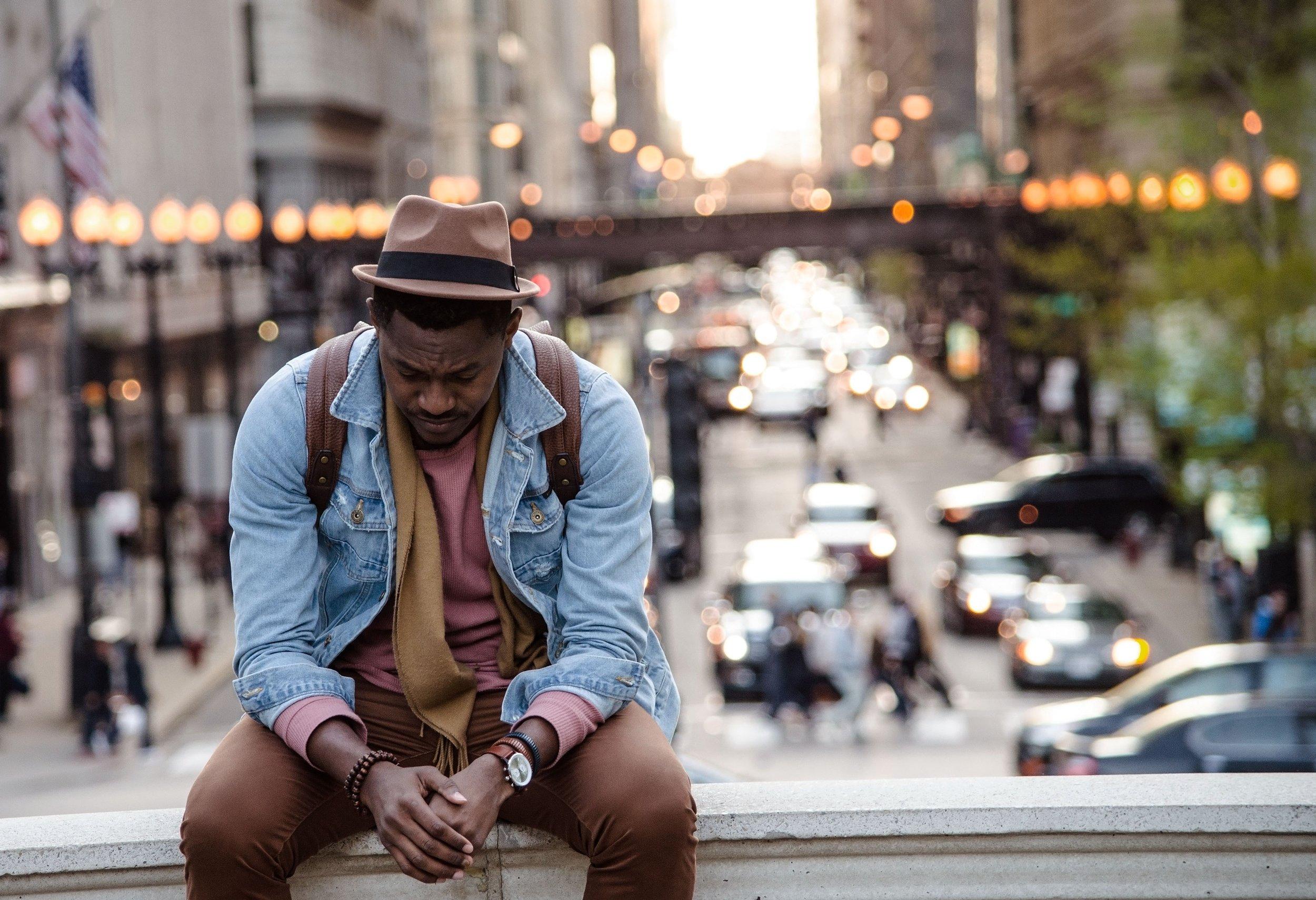 black man looking downwards sitting on ledge