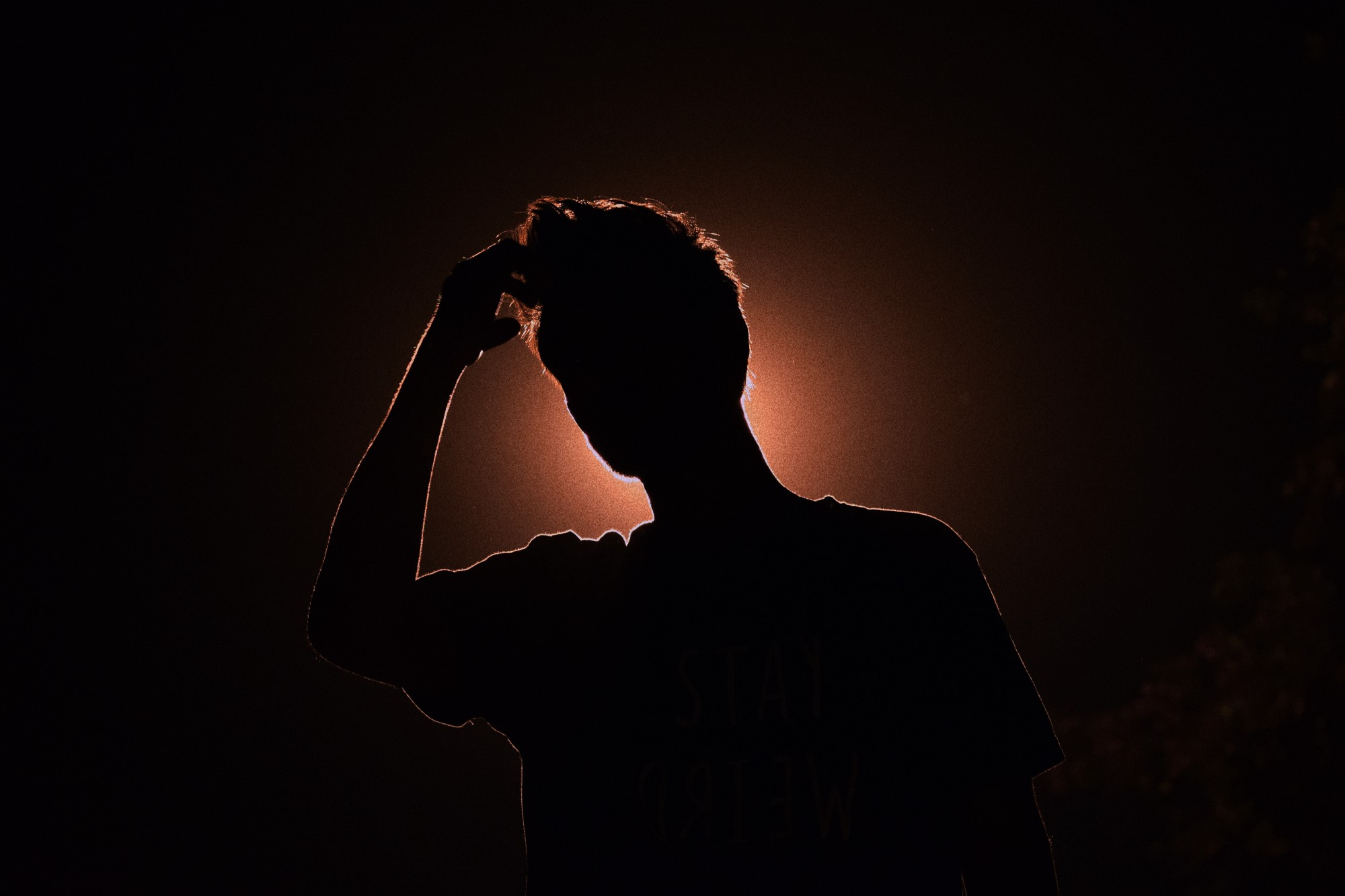 silhouette of anxious man scratching his head
