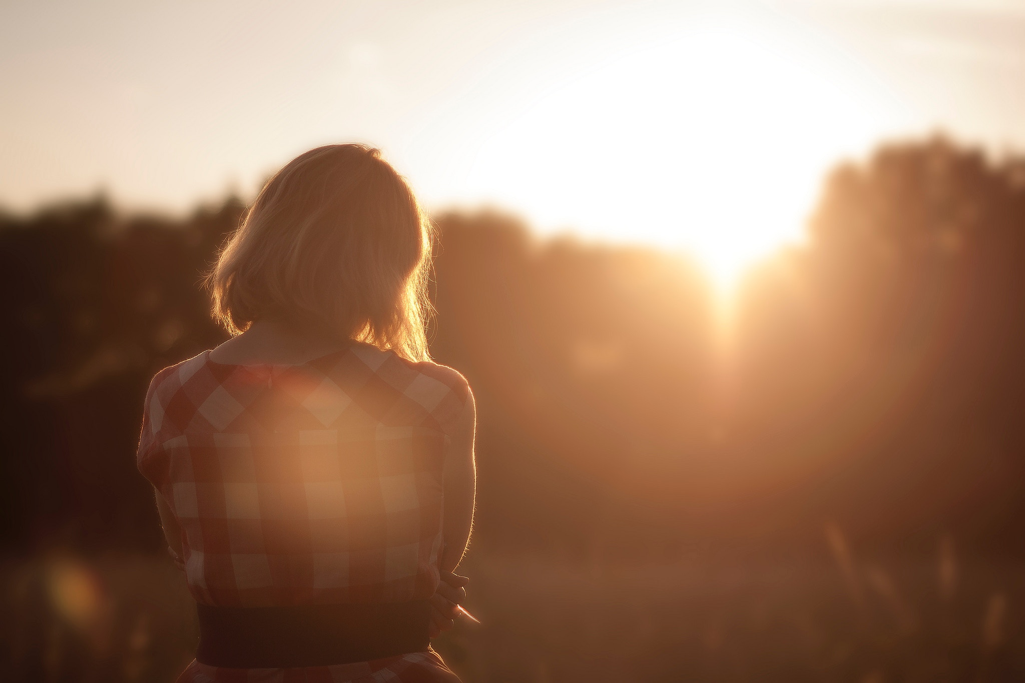 woman with mental illness looking at sunrise through trees