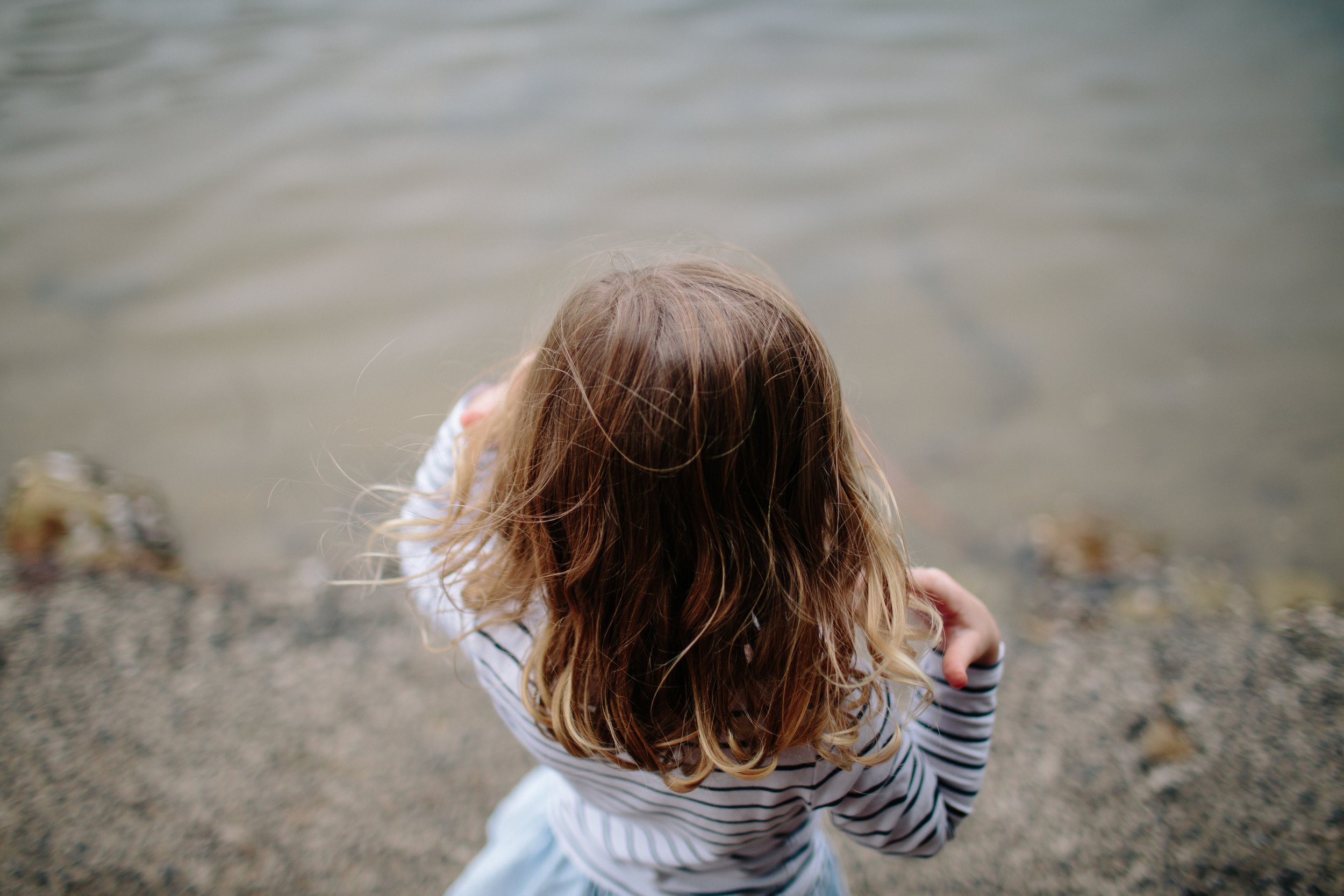 little girl who survived childhood trauma looking down at water
