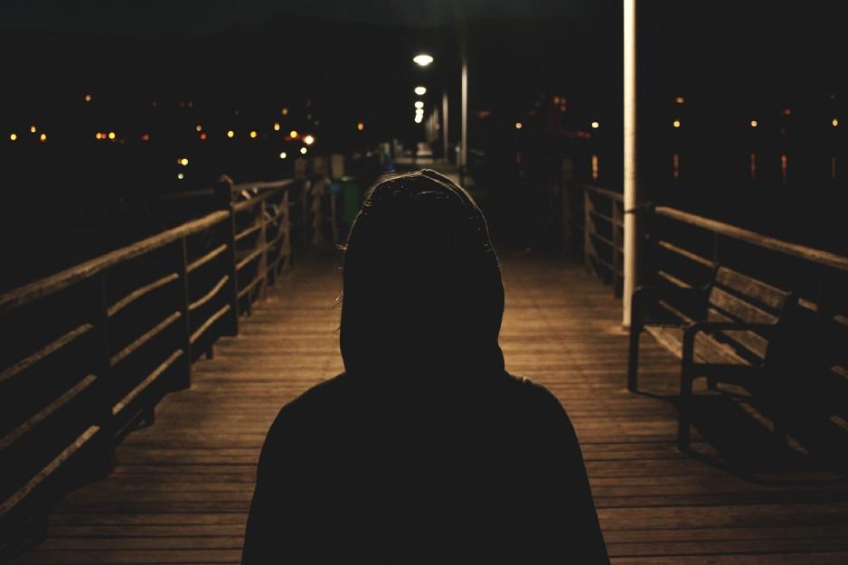anxious person walking on boardwalk at night