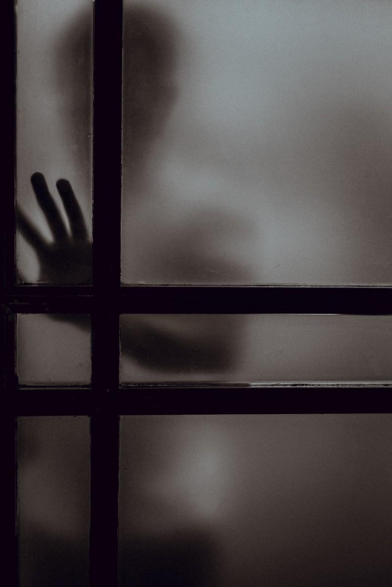shadowy figure pushing on door