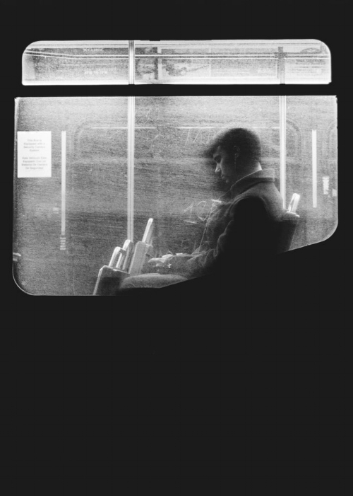 man with anxiety alone on train looking at his phone