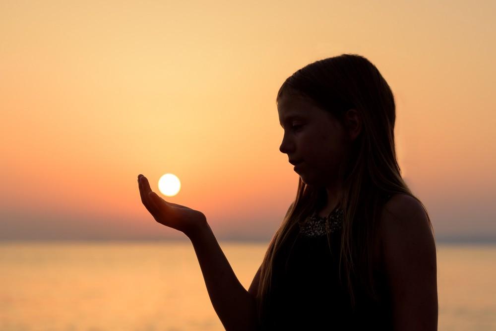 girl holding sun in her hand