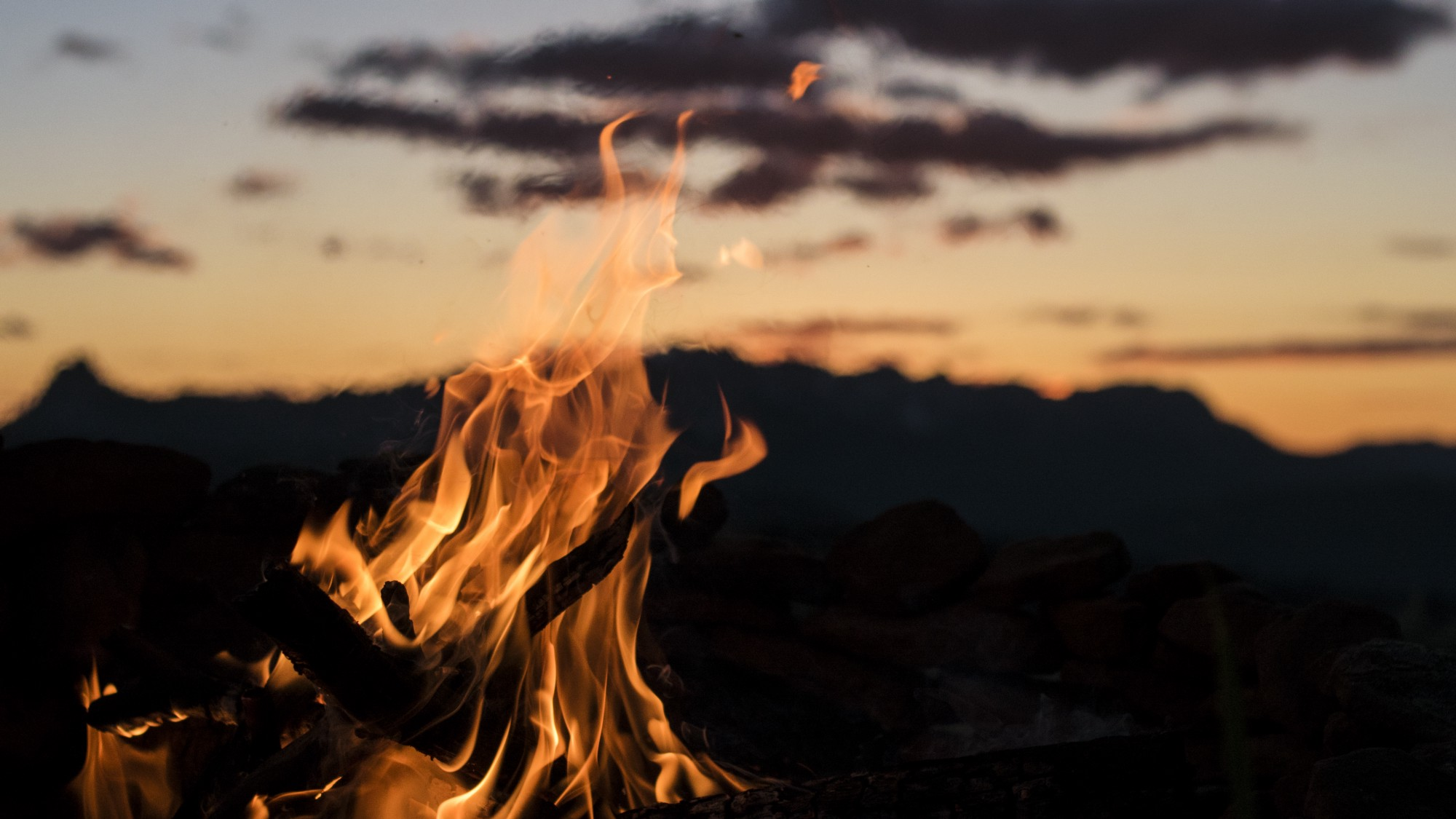 campfire with mountain range in the distance