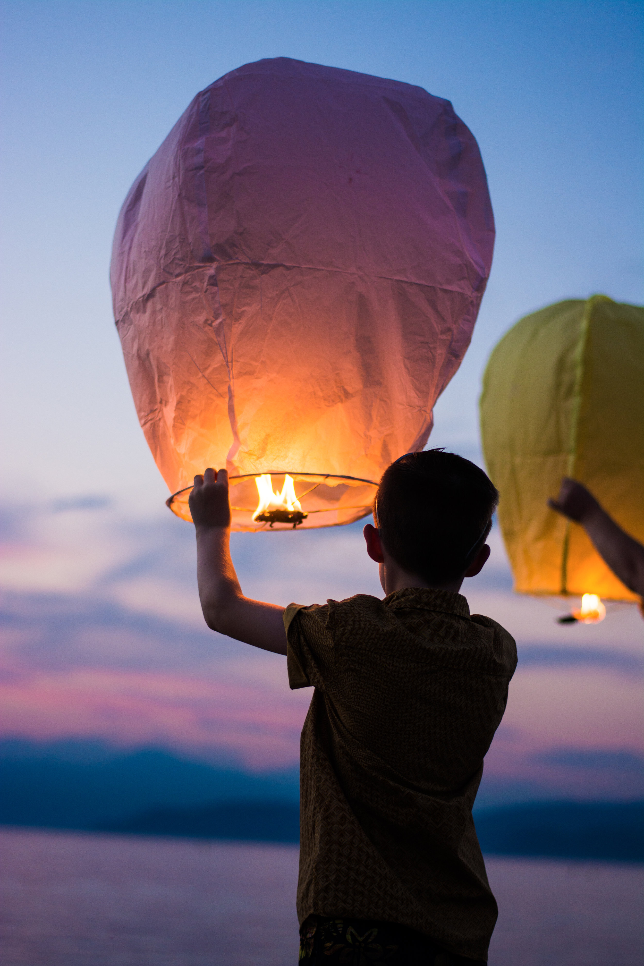 boy letting go of paper balloon