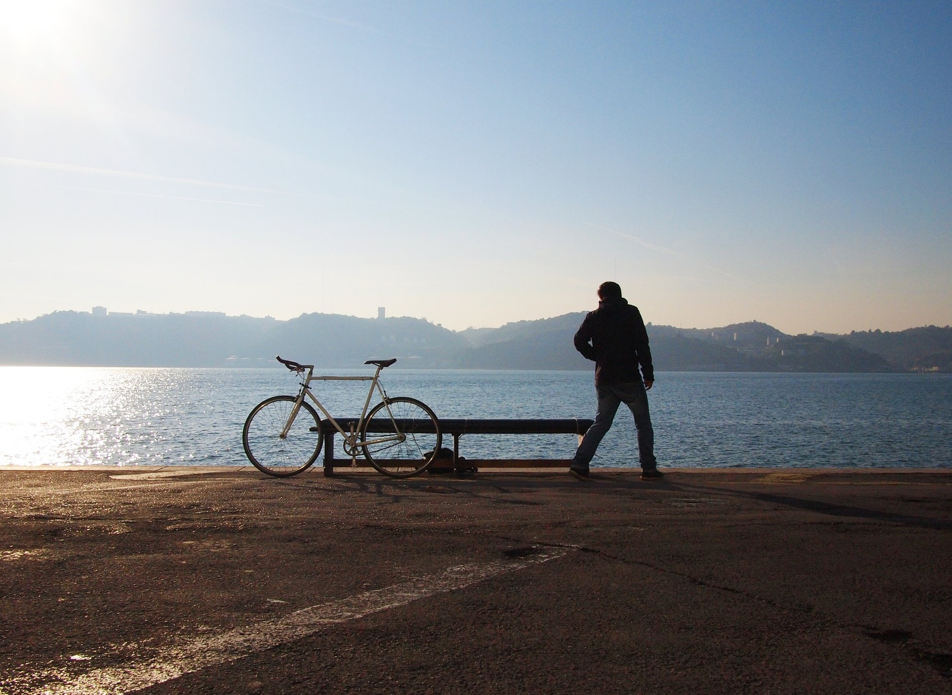 man standing next to bike along looking at water