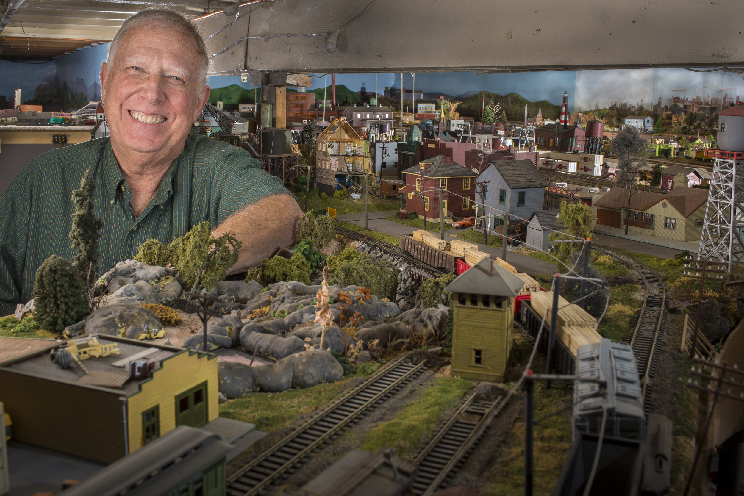 Harley Watts, 73, of Glenburn, Maine has been interested in trains from a young age. With his father working for the Santa Fe Railroad in Iowa, Watts and his brother spent many hours at the train station with their dad, hoping to spot the smoke of the steam engines as they arrived. His fascination with trains and even his perspective of those trains from when he was younger became a hobby he still enjoys today. After joining the Peace Corps in the 1960s to assist agriculture in India for a couple years, Watts then joined the Army before moving to Maine. The layouts, which fill his basement, are built so that you can walk through them at eye level. This perspective is reminiscent of how he saw trains as a kid, and allows others to share that perspective. His collection, including roughly 800 feet of track, 20 diesel engines, 10 steam engines and at least 240 cars snakes through the various towns he's created—with Watts' sense of humor sprinkled throughout the designs as visual jokes. If you know Harley Watts well, there's a good chance something in one of his towns will bare your name. Watts has visited 16 countries, earned a degree in Political Science from the University of Maine, retired from a 20-year career with GE, been married for nearly 50 years and shares his passions with four children and six grandchildren.