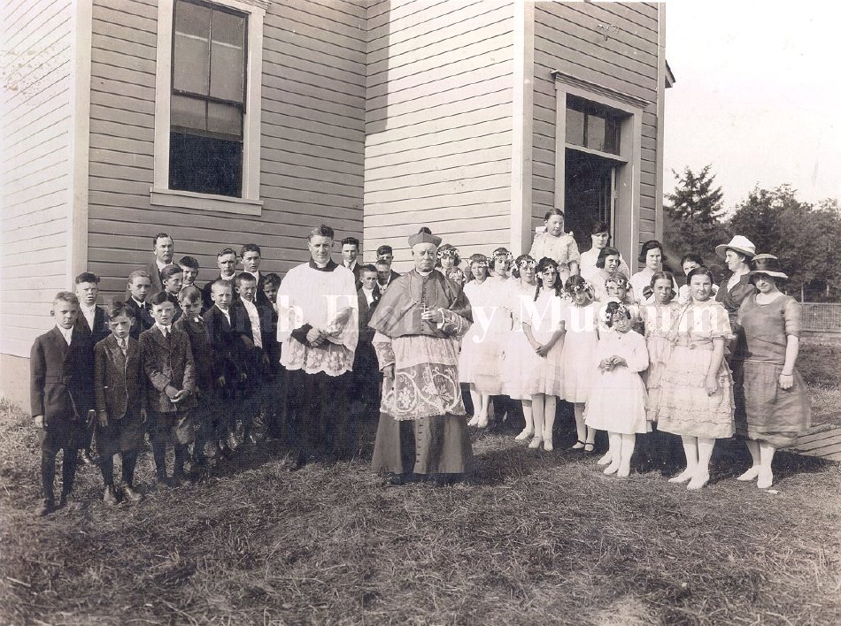 Children and adults standing in front of St. Joseph Catholic Church, ca 1920. The priest next to the high official is Father Carey. Also present in the photo are Joseph Rutkowski (front row, far left), Joe Neukirchen (adult male in back row, beneath window), Joseph Donlan (directly in front of Joe Neukirchen), John Hircko (the closest to the front of the four boys between the Bishop and Father Carey), Mary Lotto (just behind the Bishop's shoulder, the first of the little girls), Alice Neukirchen (back row, standing on something to make her the tallest in the back row, closest to the window on the right), Anne Rutkowski (directly behind the shorter girl in the front row), Marie Neukirchen (to Annie Rutkowski's left), and Anna Suess (Mrs. Joe) Neukirchen (second from the right, wearing the white hat). [IHM photo 96-15-1] From Issaquah History Museum.