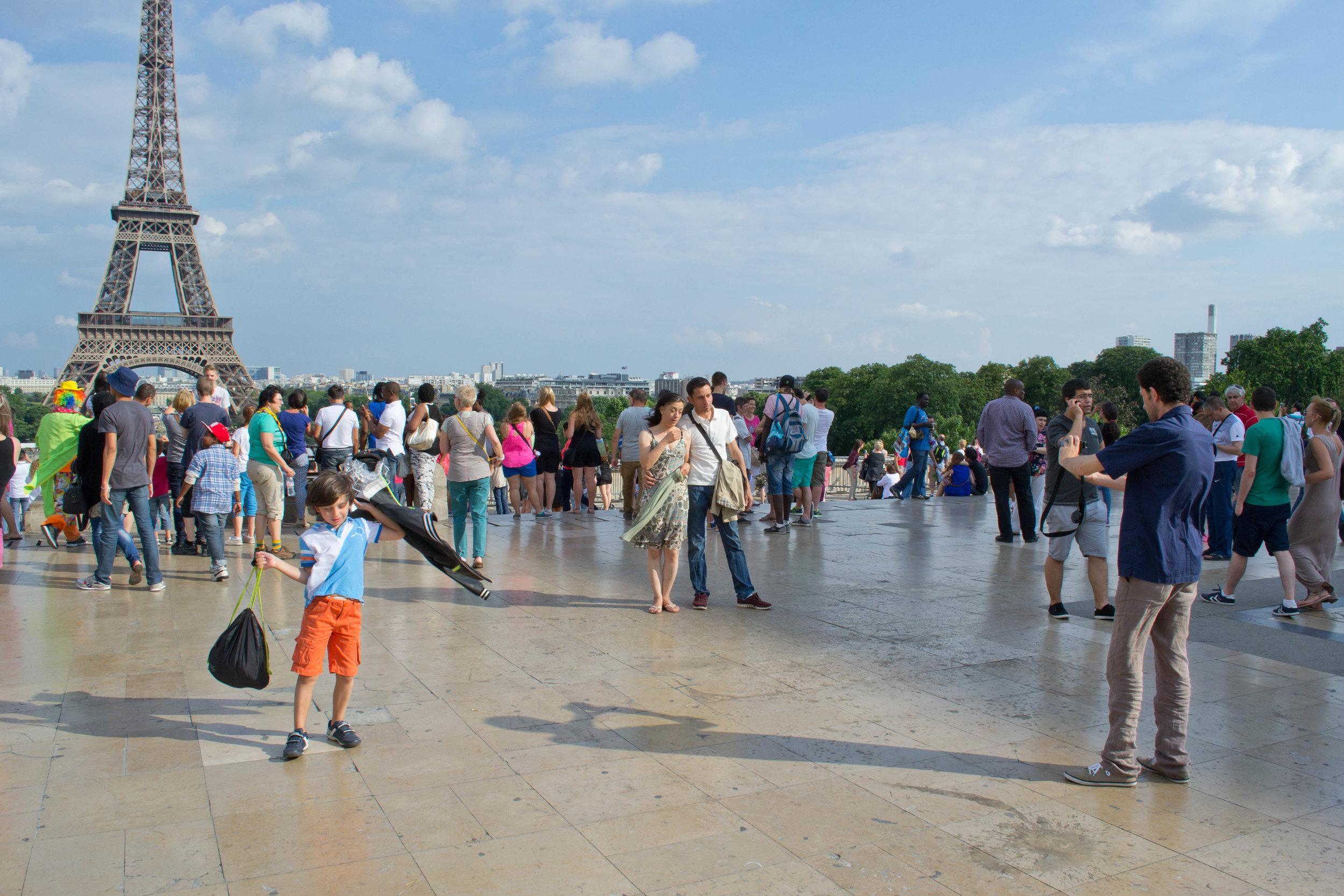 Nabil tager et billede af to af hans venner fra smuglerbåden foran Eiffeltårnet, mens kvindens søn svinger rundt om sig selv. De rejste hver for sig gennem Europa men blev genforenet for en dag i Paris.Foto: Rasmus Bøgeskov Larsen