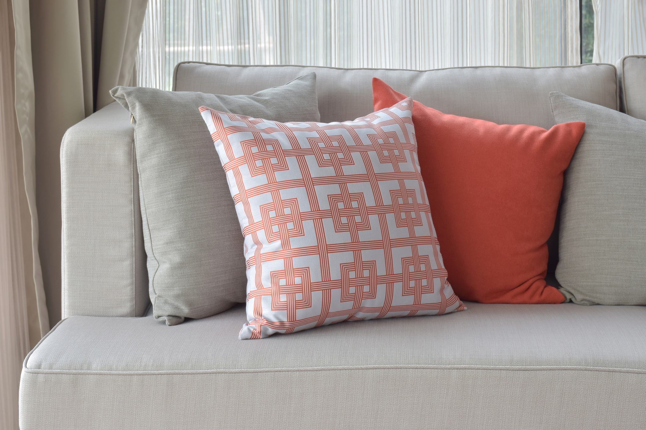 Clean gray couch and orange pillows cleaned by Columbia Carpet Cleaning