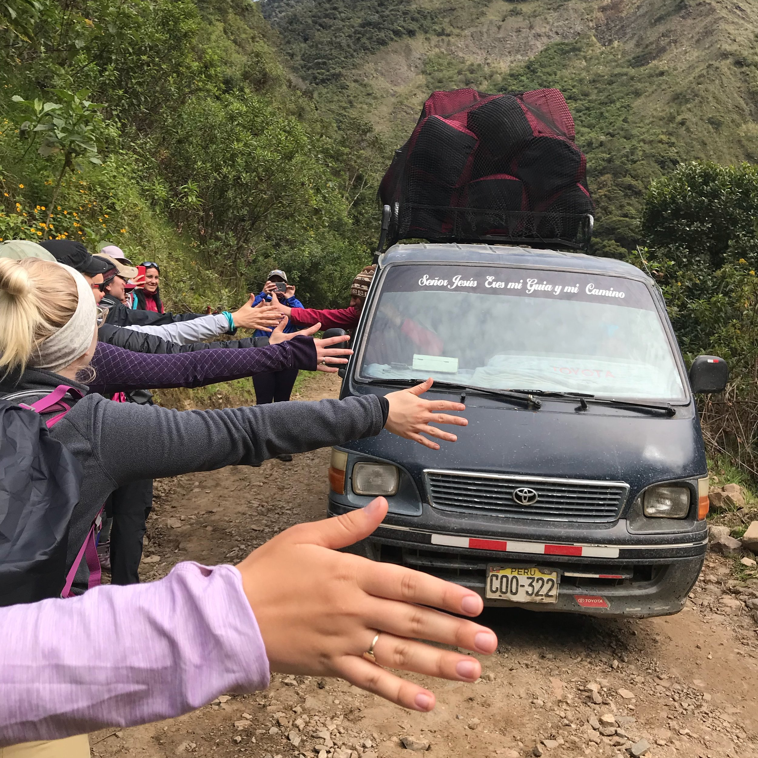 "We lined up to give our crew ""high fives"" as they transported our gear down the trail for the last stretch of the trek. Unlike other international summits, the crew does not carry gear but instead they are in charge of leading the horses and mules (and in this photo, the van) that carry all of our gear."
