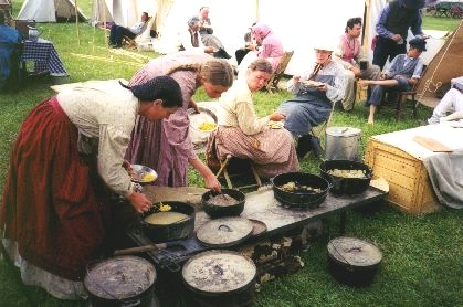 """Made July 1997 at Fort Bridger Wyoming.  Re-enactors in the """"Authentic Camp."""" Photograph by Steve Berlin.  The """"Authentic Camp"""" docents from Old Deseret Village at The Place State Park in Salt Lake City, Utah. They are shown having a pioneer supper. This living history group was with the company throughout the trek and adhered as closely as possible to the means and methods of pioneer times."""