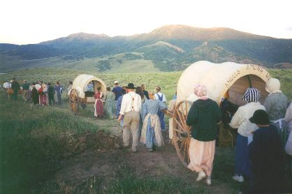 Made July 22, 1997 just north of East Canyon Reservoir. Handcart Company,   East Canyon, UT.   Photograph by Steve Berlin.  As dawn breaks across the Wasatch Range and the morning sun's first rays touch the mountain tops, the handcart company is on its way. First comes the long, steep pull to the top of Big Mountain and in the afternoon, the hot climb up Little Mountain where they will camp for the night.