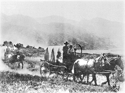 Made July 2, 1897 near mouth of Emigration Canyon, Salt Lake City, Utah.  Used by permission, Utah State Historical Society, all rights reserved - Photograph: Salt Lake Tribune.  Just as one would do so 100 years later, in 1897 for the 50-year Silver Jubilee Celebration of the Mormon Trail, a re-enactment wagon train enters the Salt Lake Valley. This view is looking generally south from the bench north of Emigration Canyon.