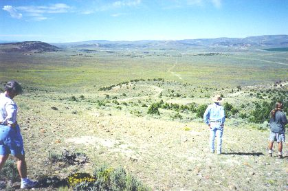2. Made about ten miles SW of Fort Bridger, WY, 8/23/97. Gravel Hill Bigelow Bench.  Photograph by Steve Berlin.   View from Bigelow Bench looking a little south of west. After climbing up from Fort Bridger onto the bench the trail traverses several miles of largely flatland before descending from this point to Muddy Creek, several miles beyond. This was a very steep descent and over time, required considerable road building to make the trail relatively safe, as well as useful for travel in both directions. The track crossing the grass and sagebrush plain to the right of center is the trail. It has seen considerable use this year by folks recreating the handcart experience. The Muddy lies in the distance where a few dark trees can barely be seen just above the plain. The stream flows left to right (south to north).