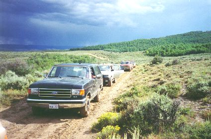 "10. Made August 23, 1997 near Quaking Aspen Ridge, WY, SW of Ft. Bridger, WY. Caravan Near Quaking.  Photograph by Steve Berlin.  The field trip caravan consisted of about 15 four-wheel-drive vehicles, most carrying several members. Here we are seen on Quaking Aspen Ridge near the place where the trail veers off the ridge, climbs a little more and starts a steep descent. A sprinkle of rain has made the road slick. The view from the high ridge is beautiful and vast in all directions. This route was used by, among others, Brigham Young.   ""About 3 o'clock we resumed our journey starting up the valley; we passed over a small hill, and then ascended the dividing ridge by a zigzag road. A she bear and two cubs were seen by Brother Cloward going (up) a high hill on our left hand. We descended by two steep pitches, almost perpendicular, which on looking back from the bottom looks like jumping off the roof of a house to the middle story and then from the middle story to the ground. Thank God no accident happened."" (They had locked their wheels for over 1/2 mile)  - Thomas Bullock journal of July 10, 1847"