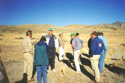 2. Made 10/18/97 at Crossroads kiosk site, ~20 miles north of Wendover, UT.  Bidwell-Bartleson Route.  Photograph by Steve Berlin.  View looking west. Roy Tea, our field trip guide, talks to the group. On this site located in Nevada a few miles south of Donner Spring, Utah, the Crossroads Chapter will erect an interpretive kiosk to educate the public about this significant section of trail. The trace that traverses the photograph from right to left was pioneered by the Bidwell-Bartelson Party of 1841 the first overland emigrants to California, is the road taken by the Donner Party and others in 1846 and by at least hundreds of argonauts bound for California during the Gold Rush years of 1849-50.