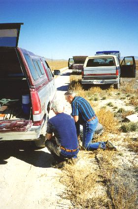 """8. Made 10/18/97 , just east of Lucin, UT.Al Mulder Gets a Flat.  Photograph by Steve Berlin.  No sooner had we started along the old roadbed when crackling over the CB came the message, """"Flat tire!"""" We'd been warned about the possibility that old spikes from the railway could still be lying about and could puncture a tire with ease, but we weren't prepared for how many flat tires we would have and just how devastating most of the punctures were. Before the day was out our group of 15 vehicles had experienced 8 flats! The damage was so great that in most cases treads and sidewalls were shredded making repair of the tires impossible.  In this picture Al Mulder goes to work after stopping for someone else's flat and finding one of his own tires was leaking too. Al's was the gentlest of the day's flats - most were blowouts."""