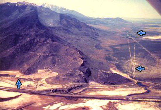 3. Made May 1979, Looking SW Timpie Point, Skull Valley, UT.  Photograph: Copyright © 1979 Roy D. Tea.   Looking south. Timpie Point, the northernmost extent of the Stansbury Range is at bottom center. Big Springs is at bottom right below the arrow and just right of the dirt road with the sweeping curve. The Hastings Trail is marked by blue arrows. The straight line to its left is the Lincoln Highway. The trail crosses the straight line on the right which is the county road to Dugway Proving Grounds. Timpie Point is where Jedediah Smith came in 1827 after crossing Nevada from California. As it rounds the point, the trail is found hugging the mountain and there are several sections of nice ruts (arrow at left). OCTA Carsonite markers stand in several places where the trail can be positively located here.