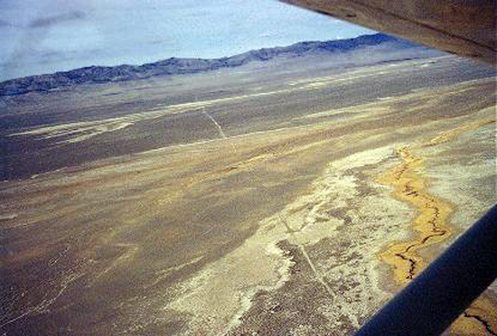 """4.Made 1971,Looking NW at Skull Valley, UT.  Photograph: Copyright © 1971 Roy D. Tea.   This photograph was taken above Skull Valley several miles south of the previous one. Having proceeded south into Skull Valley far enough to skirt the wetlands, the Hastings Trail is seen here angling sharply back to the northwest as it leaves the area of Hope Wells. Hastings Pass through the Cedar Mountains is the low area in about the center of the skyline to the right of the trail's line. A tiny flow from Redlum Spring in the foothills of the Cedars was the only water known to emigrants between here and Donner Spring nearly 80 miles beyond.  Beneath the airplane is about the place where Eliza P. Donner Houghton of the Donner Party describes her mother piecing together a note left by Hastings that appeared to have been shredded by birds: """"2 days--2 nights--hard driving--cross--desert--reach water."""" (See Roy Tea's article on the Hastings Trail from Grantsville to Donner Spring in our Members' Pages section)."""