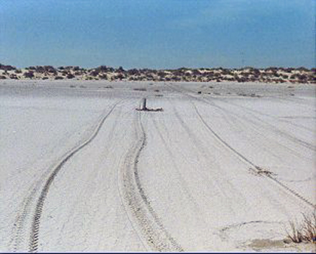 """10.Made 9/23/87 Great Salt Desert, Utah.Approaching the Dunes on the East Side.  Photograph: Copyright © 1987 Roy D. Tea.   The east side of the Great Salt Lake Desert is marked by sand dunes as well as stretches of flats. Softer ground to the north in this area prevented the emigrants from taking a direct route toward Pilot Peak, at the foot of which, they knew they would find water.  Here the trail approaches an area of dunes after passing through a small depression. To climb up on the dunes, the trail curves to the right but then straightens and proceeds nearly due west again. A 6"""" aluminum pipe can be seen near the center of the photograph which has just been placed to mark the trail by Dan Miller Jr. and Roy Tea."""