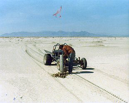 """14. Made: 9/23/87 Great Salt Lake Desert, Utah. The Big Bend.  Photograph: Copyright © 1961 Roy D. Tea.   Dan Miller Jr. setting a 6"""" aluminum pipe to mark the Hastings Trail at the Big Bend. Silver Island Range in background. Compare to previous photographs in the exhibition made at this place."""