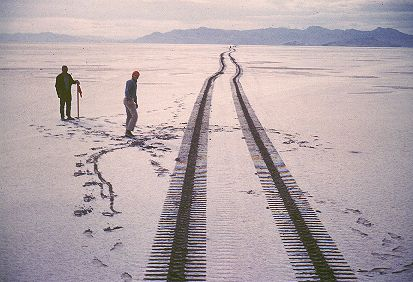 """16. Made 10/61, Great Salt Lake Desert, Utah.Marking the Road.  Photograph: Copyright © 1961 Roy D. Tea.   View looking west. Hastings/Donner-Reed Trail runs from left center to upper right, between the two men. The trail is lighter in color because it has been compacted some by the wagons and animals, allowing a little more white salt to fill the slight depressions. Floating Island is at the right and at greater distance, stretching across the right two-thirds of the skyline, is Silver Island.  Phil Marstella stands by a 2"""" X 2"""" stake he and professor Derle Thorpe of Utah State University (in the red cap) have just placed to mark the trail. The tracks were made by the Trackmaster."""