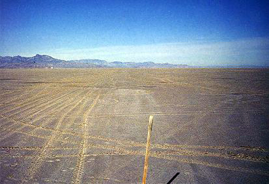 17.Made 11/5/86, Great Salt Lake Desert, Utah.The Stake Still Stands 25 Years Later.  Photograph: Copyright © 1986 Roy D. Tea.   View looking northwest. Here, 25 years later, is the stake placed in October 1961 to mark the trail. The trail is the lighter tracks in the center of the picture. Recent all-terrain-vehicle tracks are on the left. Floating Island is left of the white dot at the top of the flat and on the left.