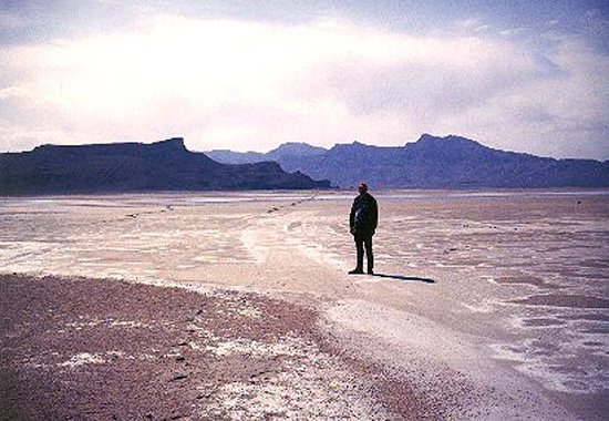 23. Made 4/30/1971, Great Salt Lake Desert, Utah.East of Silver Island.  Photograph: Copyright © 1971 Roy D. Tea.   Roy Tea stands astride the Hastings Trail which is clearly visible as it strikes out across the flat to pass the north end of Floating Island, the dark mountain on the left. To the right and at greater distance is Silver Island, named for mineral exploration there in the 19th century not for its color, which is ruddy.