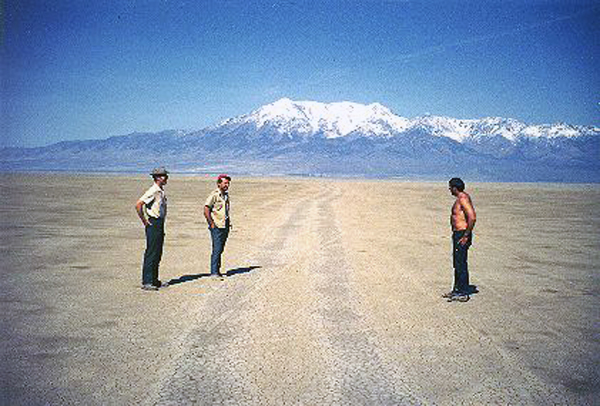 29. Made 5/1/71, Great Salt Desert, UT. Near Donner Spring.  Photograph: Copyright © 1971 Roy D. Tea.   Looking west. Here, from left to right are Bruce Bloomfield, Quinton Adair and Dan Miller, friends of Roy Tea who are interested in the trail. This mud flat is the last of the salt desert as emigrants descended from crossing Silver Island at Donner-Reed Pass and made the final push to Donner Spring. This photograph was made a couple of miles west of the pass and about seven miles from the water. Pilot Peak, 10,700 feet high and beacon for nearly 100 miles of travel, dominates the view. Donner Spring is a little beyond the far margin of the flat where trees can just be seen left of center.