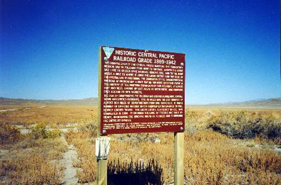 7. Made 10/18/97 , just east of Lucin, UT.BLM Sign Transcontinental RR Grade. Photograph by Steve Berlin.  The major purpose of our Fall outing was to drive more than 90 miles of roadbed from the original Transcontinental Railroad, visiting historic sites along the way. The sign at the western terminus of the driveable section, made mostly obsolete for railroad use in the early part of the century says:   HISTORIC CENTRAL PACIFIC RAILROAD GRADE 1869-1942   THE ORIGINAL GRADE OF THE CENTRAL PACIFIC RAILROAD (THE PROMONTORY BRANCH) MAY BE FOLLOWED FROM HERE TO THE EAST, AROUND THE GREAT SALT LAKE TO GOLDEN SPIKE NATIONAL HISTORIC SITE, AND TO THE WEST ABOUT A MILE TO WHERE IT JOINS THE LUCIN CUTOFF AND THE REST OF THE ORIGINAL LINE TO CALIFORNIA. THE COMPLETION OF THE TRANSCONTINENTAL RAILROAD AT PROMONTORY SUMMIT MAY BE THE MOST IMPORTANT EVENT IN THE HISTORY OF THE WESTWARD EXPANSION OF OUR COUNTRY. IT LINKED EAST AND WEST, OPENED UP VAST AREAS TO SETTLEMENT, AND PROVIDED EASY ACCESS TO NEW MARKETS.  THE TASK OF CONSTRUCTING THE RAILROAD WAS ENORMOUS REQUIRING SEVERAL YEARS AND UNTOLD HARDSHIPS. THIS 90 MILES WAS THE LAST STRETCH OF ALMOST 800 MILES OF CONSTRUCTION FROM SAN FRANCISCO. IT HAD A NUMBER OF DIFFICULT GRADES WHICH REQUIRED EXTRA ENGINES TO PULL HEAVILY LOADED TRAINS. THE LUCIN CUTOFF, CURRENTLY IN USE, WAS COMPLETED IN 1904. IT CROSSES THE LAKE BY TRESTLE AND BUILT UP GRADE, SHORTENING THE ORIGINAL ROUTE BY 40 MILES AND ELIMINATING THE DIFFICULT GRADES.  FOLLOWING COMPLETION OF THE CUTOFF, TRAFFIC DWINDLED ON THE PROMONTORY BRANCH, CONSISTING PRIMARILY OF LOCAL RESIDENTS AND LIVESTOCK. IN 1942, THE RAILS WERE REMOVED SO THE STEEL COULD BE USED IN THE WAR EFFORT.