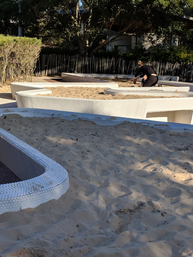 Raised sand pits inside toddler-proof fence/hedge