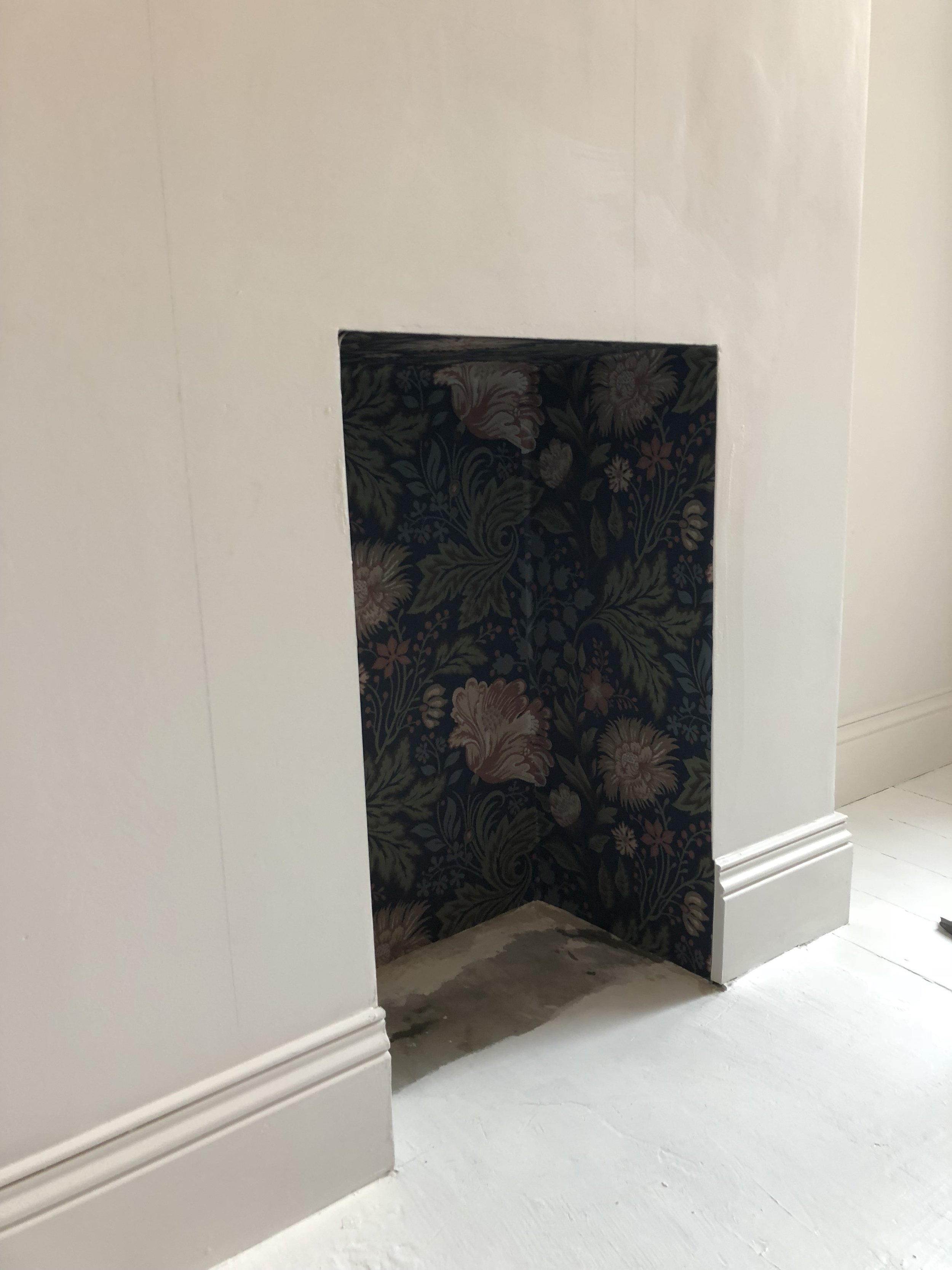 We started by wallpapering the inside of the fireplace to ensure we could match up the patterns and work around the corners