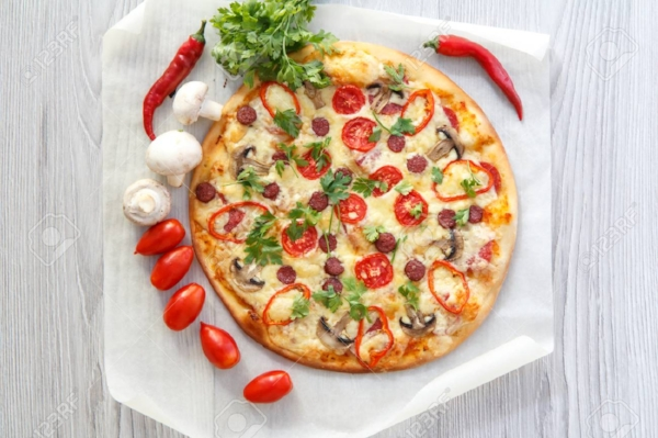 85289188-fresh-homemade-pizza-with-tomatoes-salami-cheese-and-mushrooms-with-food-ingredients-and-spices-for-.jpg