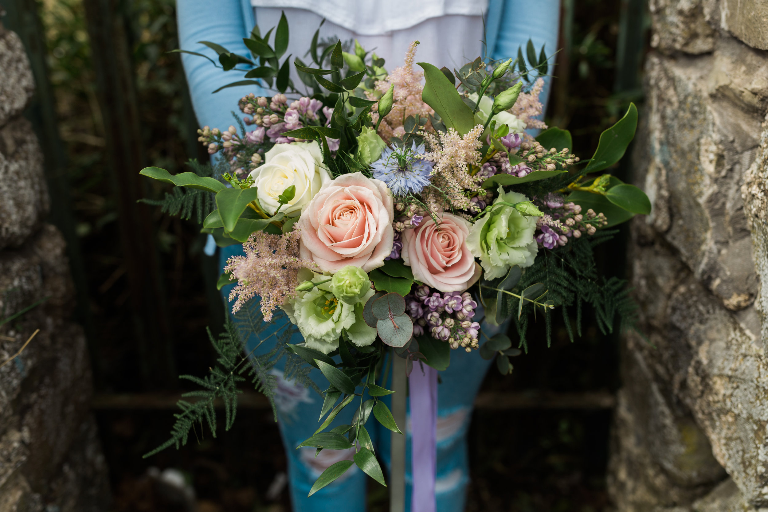 An unstructured bridal bouquet designed using a mixture of foliage, astilbe, sweet avalanche and cream avalanche roses, lilac, double eustoma & nigella.