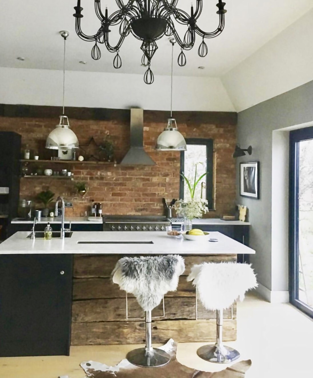 A kitchen photo from the early days of my Instagram...... We had to use what we had as we had no budget to buy anything else new for the kitchen so we spray painted a BHS chandelier black to go over the dining table and hid the white chrome stools with sheepskins.
