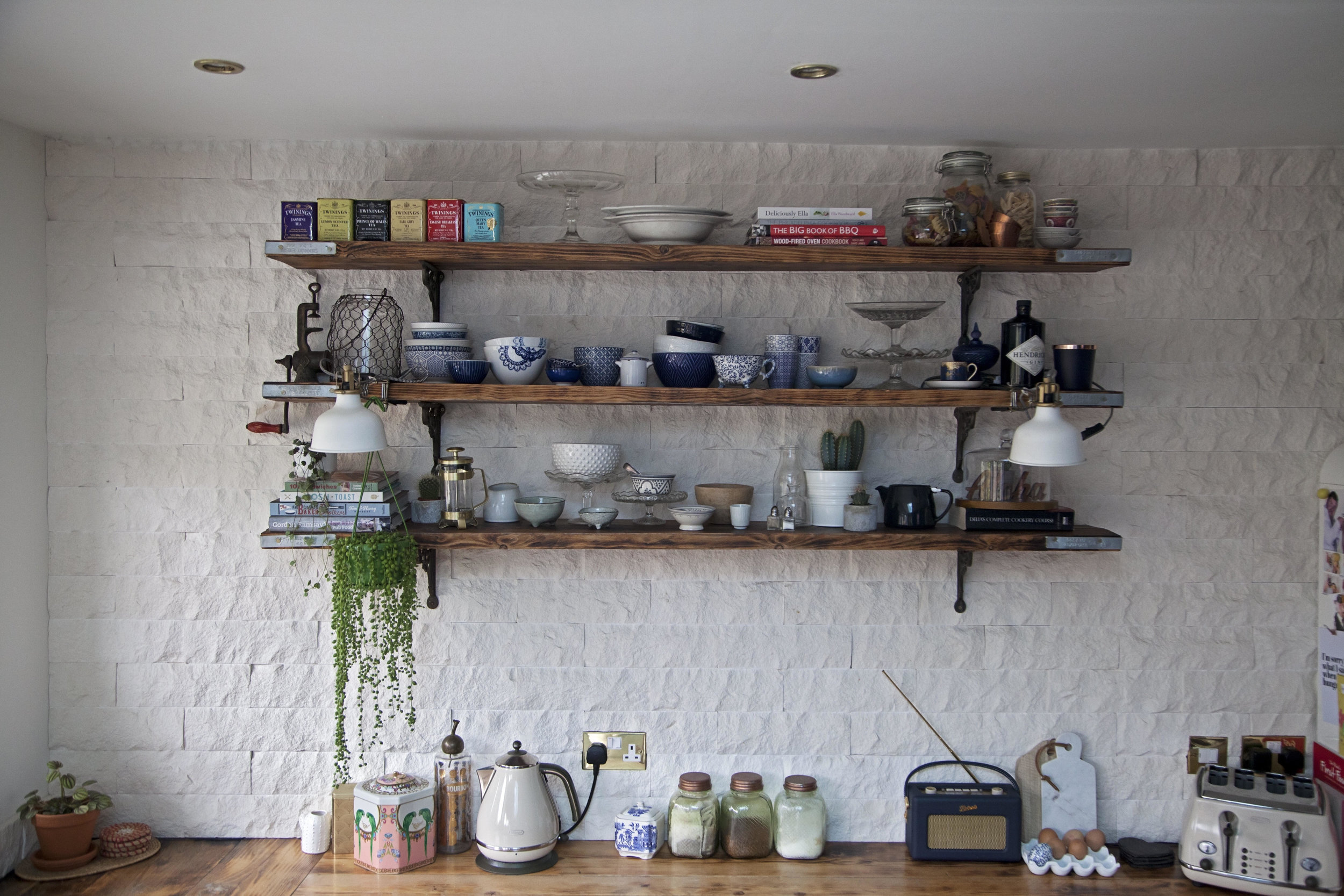 The main wall in the kitchen is fully tiled with textured split face white tiles from Mandarin Stone and features reclaimed scaffold board open shelving